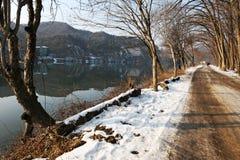 De långa går vid sjön i vinter Arkivbild