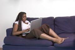 De l'adolescence avec l'ordinateur portatif sur le divan Photographie stock libre de droits