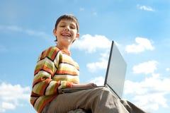 De l'adolescence heureux avec un ordinateur portatif Photos libres de droits