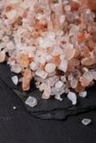 De l'Himalaya rose brut, sel de mer sur l'ardoise noire Images stock