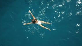 De la antena del top opinión abajo una mujer joven en una natación blanca del traje de baño en el mar Imagen de archivo libre de regalías
