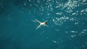 De la antena del top opinión abajo una mujer joven hermosa en un traje de baño blanco que se baña en el mar azul Fotos de archivo libres de regalías