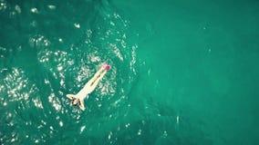De la antena del top opinión abajo una mujer joven hermosa que se baña en el mar Fotos de archivo libres de regalías