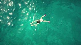 De la antena del top opinión abajo de una natación de la mujer joven en el mar Fotografía de archivo libre de regalías