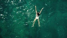 De la antena del top opinión abajo de una natación de la mujer joven en el mar Imagenes de archivo