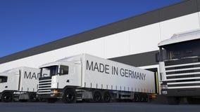 De la carga camiones semi con HECHO EN el subtítulo de ALEMANIA en el cargamento o la descarga del remolque Transporte 3D del car Imagen de archivo