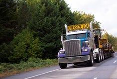 De la carga de gran tamaño del aparejo de la obra clásica camión grande semi con la cama plana descender fotos de archivo