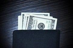 De la cartera pegue hacia fuera 100 billetes de dólar Imágenes de archivo libres de regalías