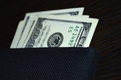 De la cartera pegue hacia fuera 100 billetes de dólar Imagen de archivo