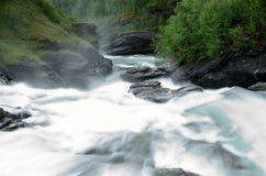 De la cascada rocas y piedras resbaladizas largas masivas blancas lechosas del valle abajo en verano Imagen de archivo libre de regalías