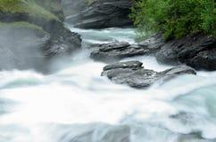 De la cascada rocas y piedras resbaladizas largas masivas blancas lechosas del valle abajo en verano Fotografía de archivo libre de regalías