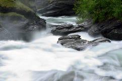 De la cascada rocas y piedras resbaladizas largas masivas blancas lechosas del valle abajo en verano Foto de archivo libre de regalías