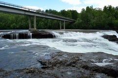 De la cascada rocas y piedras resbaladizas largas masivas blancas lechosas del valle abajo en verano con el puente del coche Imagenes de archivo