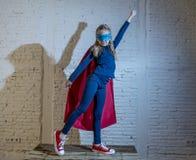 De la chica joven del niño 7 o 8 años femeninos que realiza el casquillo y la máscara que llevan de presentación felices y emocio Foto de archivo libre de regalías