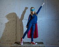 De la chica joven del niño 7 o 8 años femeninos que realiza el casquillo y la máscara que llevan de presentación felices y emocio Fotografía de archivo libre de regalías
