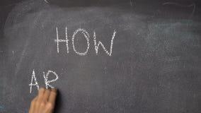 ¿` De la escritura de la mano CÓMO ESTÁ USTED? ` en la pizarra negra almacen de video