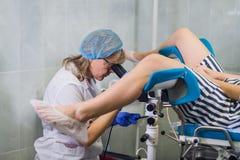 De la hembra ginecólogo mayor positivamente que examina a un paciente en la clínica, concepto de la atención sanitaria Imagenes de archivo