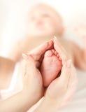De la madre de las manos pie del bebé del mantiene cuidadosamente Fotografía de archivo libre de regalías