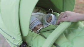 De la madre mirada joven cuidadosamente en el pequeño niño que duerme en el cochecito mientras que camina en parque del otoño almacen de metraje de vídeo
