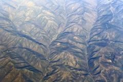 De la mucha altitud, pasando por alto las montañas Imagen de archivo libre de regalías