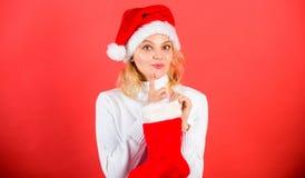 De la muchacha de la cara del control regalo alegre hacia fuera en calcetín de la Navidad Compruebe el contenido de la media de l fotos de archivo
