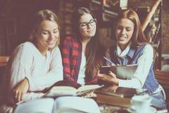 De la muchacha joven sonriente de tres preparación de trabajo estudiantes junto foto de archivo
