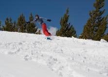 De la mujer de la snowboard colina nevosa abajo en las montañas Imágenes de archivo libres de regalías