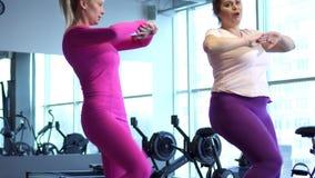 De la mujer ejercicios gordos intenso para la pérdida de peso con el instructor personal en gimnasio almacen de video