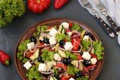 De la salade grecque est située sur un plat sur un fond foncé photos stock