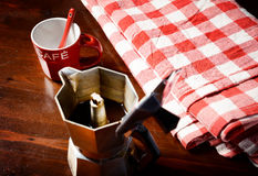 De la servilleta a cuadros en la tabla de madera con la taza de café roja Imagen de archivo libre de regalías