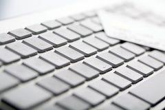 De la tarjeta de crédito en un teclado de ordenador Fotos de archivo libres de regalías