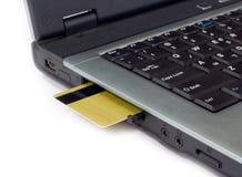 De la tarjeta de crédito insertada en computadora portátil Imagen de archivo