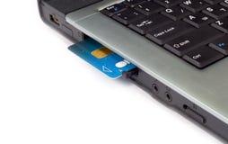 De la tarjeta de crédito insertada en computadora portátil Foto de archivo libre de regalías