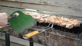 De la viande appétissante de poulet est faite frire sur le gril, un homme éventant le feu pour la chaleur banque de vidéos