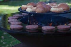 De la viande et des petits pains d'hamburger sont grillés sur le gril En dehors de la cuisson et du barbecue Repas sur le gril Pe image stock