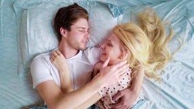 De la visión del enfoque pares jovenes superiores hacia fuera en cama por la mañana que sonríe en uno a metrajes