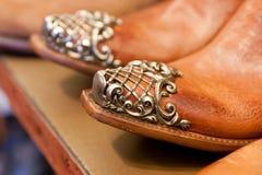 De laarzen van de close-upcowboy op een plank in een opslag stock afbeelding