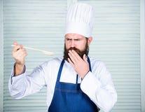 De laatste details Het gezonde voedsel koken Gebaarde mensenkok in culinaire keuken, Chef-kokmens in hoed Geheim smaakrecept royalty-vrije stock afbeeldingen
