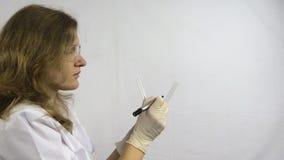 De laboratoriumvrouw schrijft identificatienummers op fles in laboratorium stock videobeelden