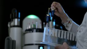 De laboratoriumvrouw trekt de buis met bacteriën en virussen terug De wetenschapper zet uit een glasfles van het koelen van doos  stock footage