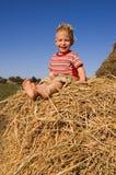 De lachende blootvoetse babyjongen zit op een hooiberg Royalty-vrije Stock Afbeeldingen