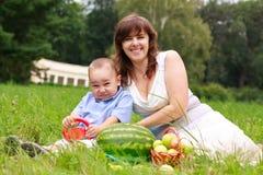 De lachende familie die van de liefde picknick in de zomerpark heeft Royalty-vrije Stock Afbeeldingen