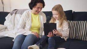 De lachende hogere grootmoeder en het leuke kleinkind letten op grappige video op tablet stock video
