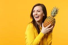 De lachende jonge vrouw die in vrijetijdskleding, greep in fruit van de handen het verse rijpe ananas isoleerde op geeloranje opz royalty-vrije stock foto