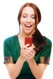 De lachende jonge vrouw leest sms Stock Foto