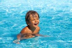 De lachende jongen met positieve emoties zwemt in pool Stock Fotografie