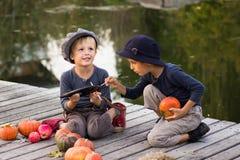 De lachende kinderen schilderen kleine Halloween-pompoenen Stock Afbeeldingen