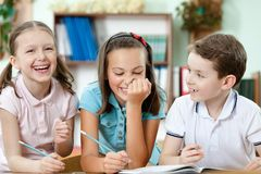 De lachende leerlingen helpen aan elkaar Royalty-vrije Stock Afbeeldingen
