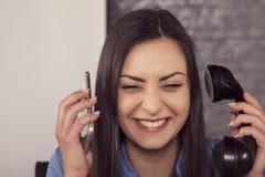 De lachende onderneemster leidt gesprekken meer dan twee telefoons stock fotografie