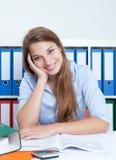 De lachende vrouw met blond haar op kantoor heeft een onderbreking Royalty-vrije Stock Afbeelding